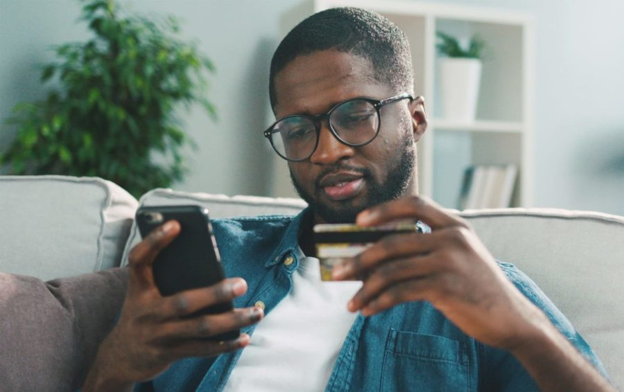 A man hold a credit card while using a cell phone