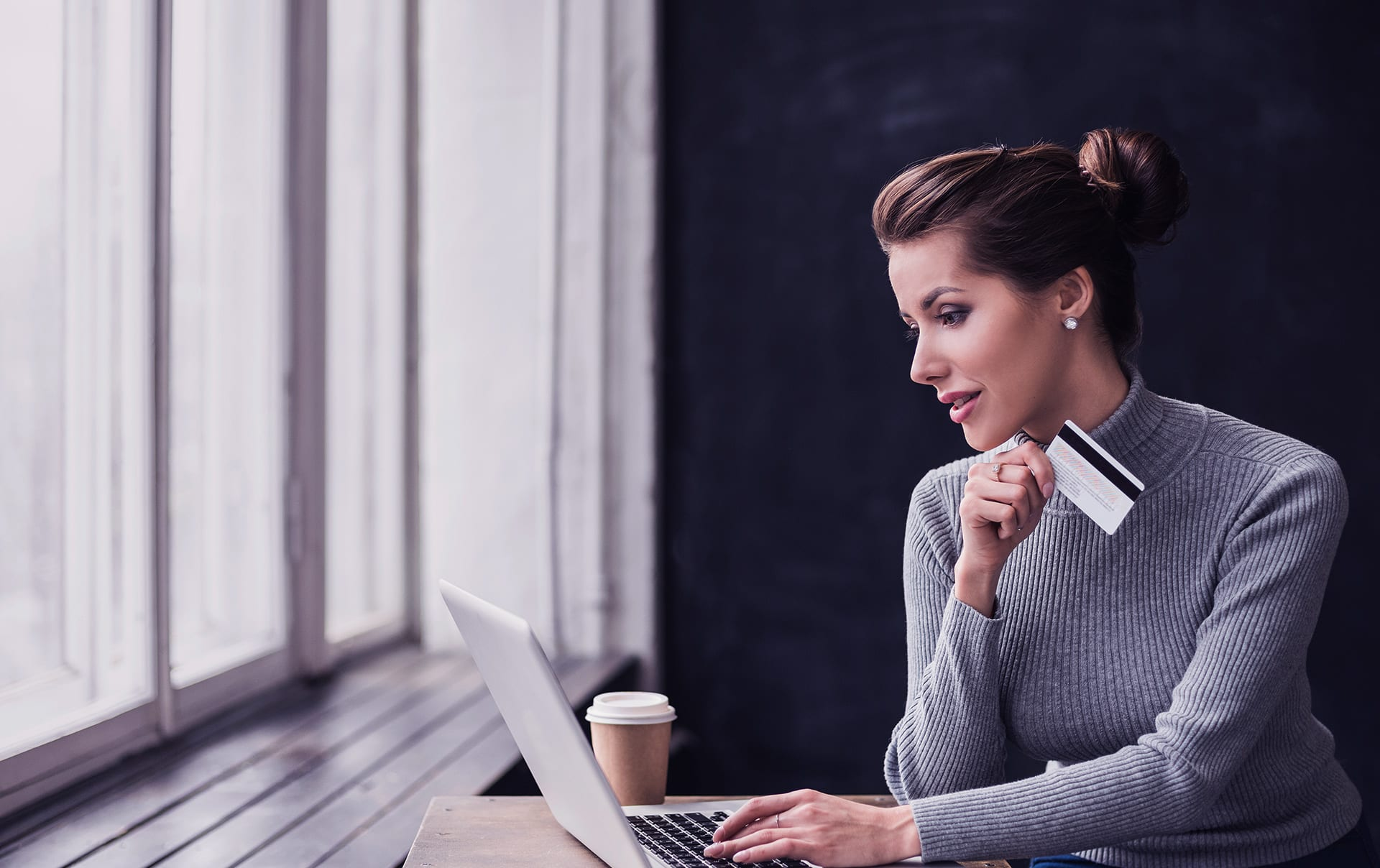 a woman holds a credit card and uses her laptop