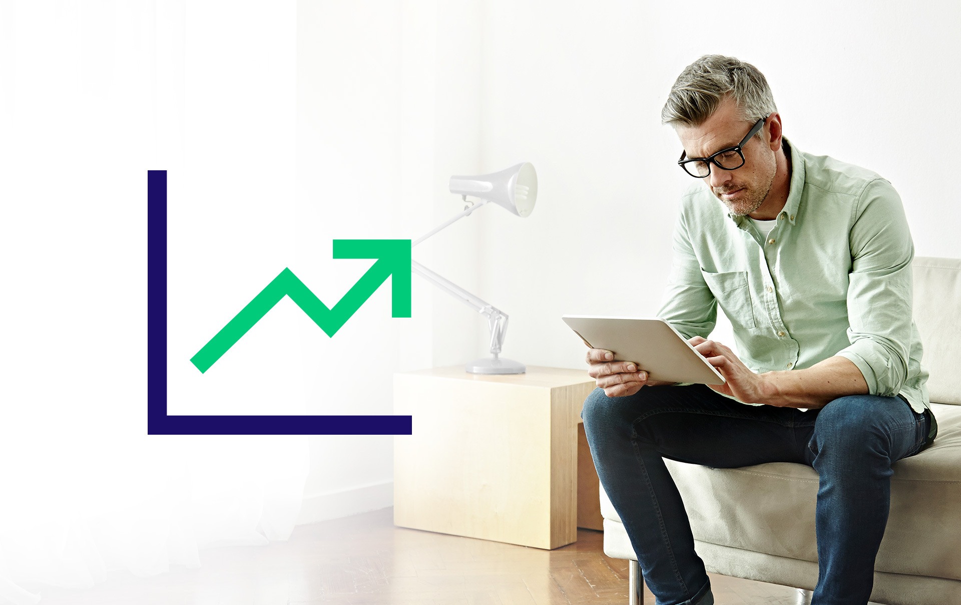 A man works on his tablet and a graphic of a line graphic trends upwards