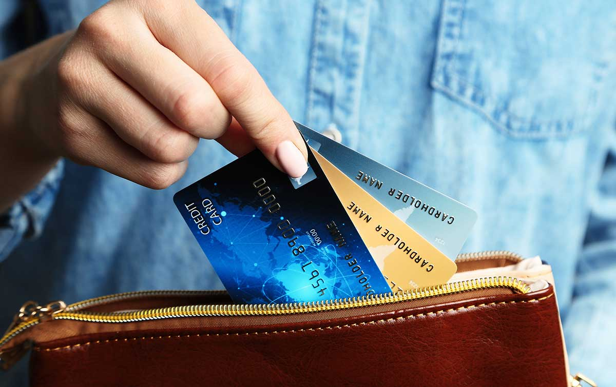 3 credit cards are being pulled out of a wallet